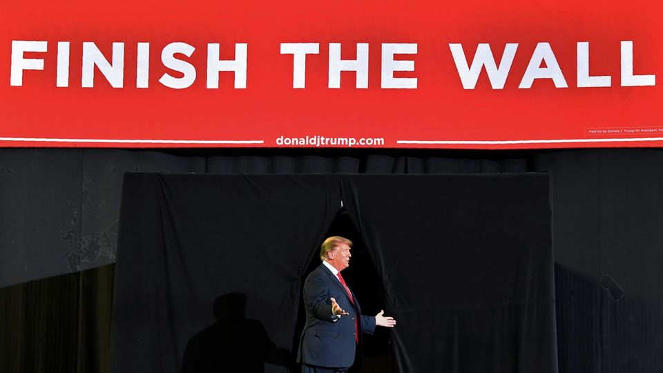 Donald Trump unter Finish the wall-Banner