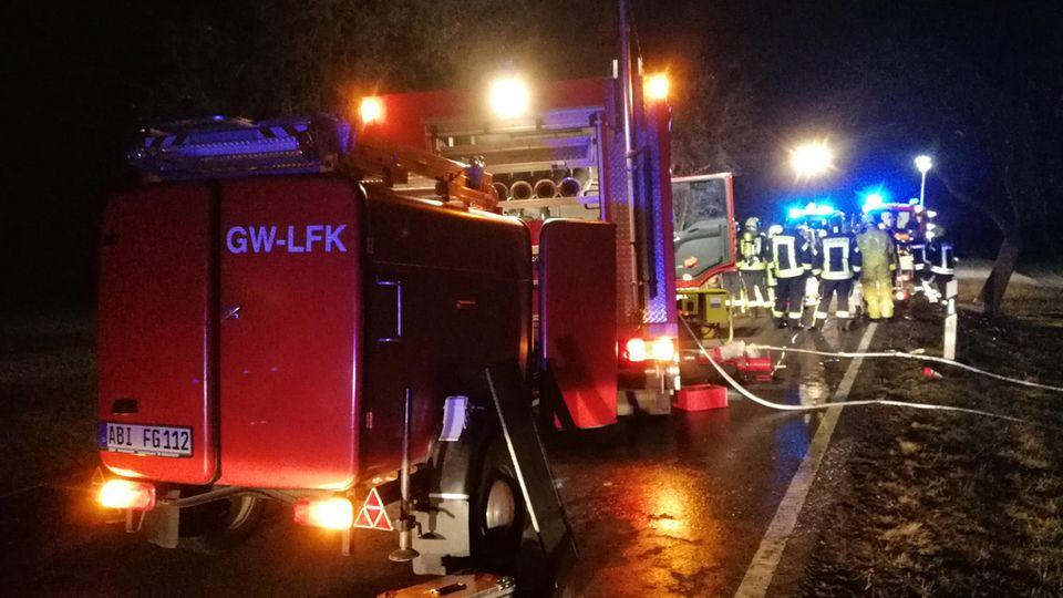 Ein Feuerwehrauto steht mit Blaulicht und Warnblinkern auf einer Straße. Im Hintergrund ist eine Gruppe Feuerwehrleute zu sehen