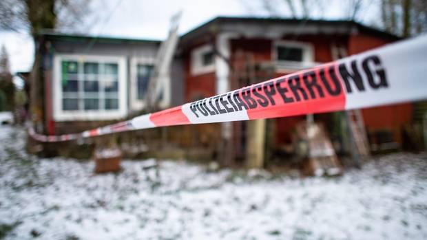 """Vor einer rostroten Holzhütte hängt ein Absperrband """"Polizeiabsperrung"""". Auf dem Rasen vor der Hütte liegt Schnee"""
