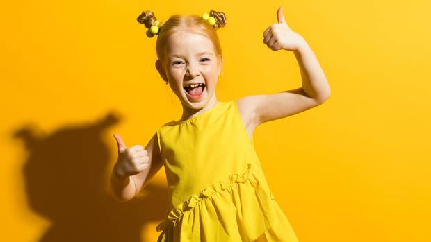 Kind mit roten Haaren zeigt einen ausgestreckten Daumen in die Kamera