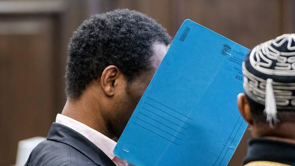 Ein Mann sitzt in einem Gerichtssaal und hält sich einen blauen Pappordner vors Gesicht