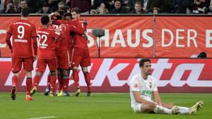 Augsburgs Rani Khedira (r.) sitzt niedergeschlagen auf dem Rasen, während die Bayern-Spieler jubeln