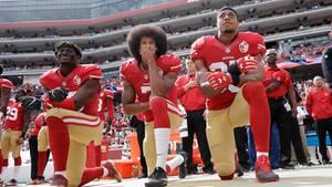 Drei Spieler des NFL-Teams San Francscio 49ers knien am Spielfeldrand
