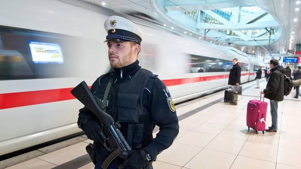 Ein Bundespolizist mit Gewehr in den Händen steht am Fernbahnhof des Frankfurter Flughafens an einem ICE