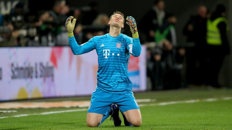 Torwart Manuel Neuer kniet auf dem Rasen und schaut mit erhobenen Armen zum Himmel