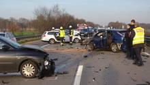 Auf einer Autobahn sind Polizisten und Feuerwehrleute zwischen vier Autowracks unterwegs