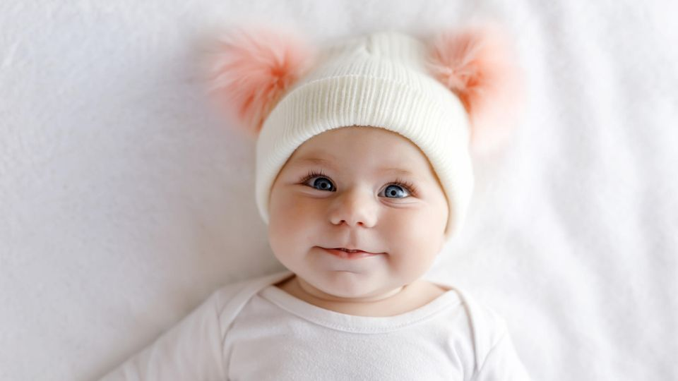 Ein Baby strahlt mit großen Augen in die Kamera