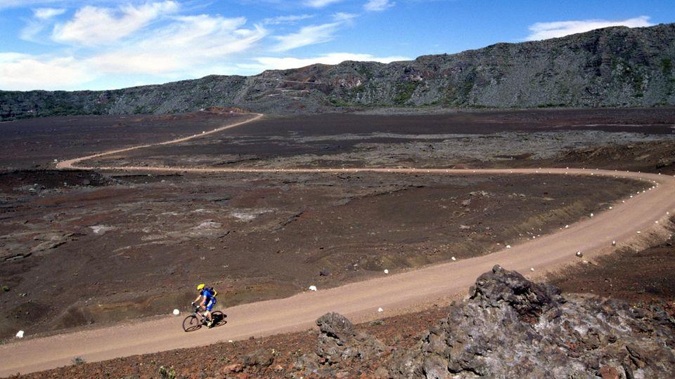 Ein einsamerMountainbiker in derPlainedes Sables aufLa Réunion im IndischenOzean,