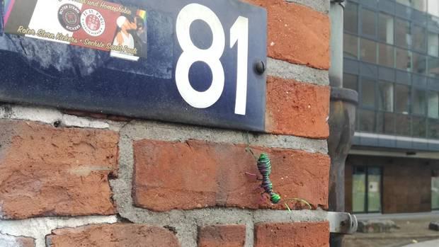 Eine Ameise aus Draht sitzt an einer Hauswand