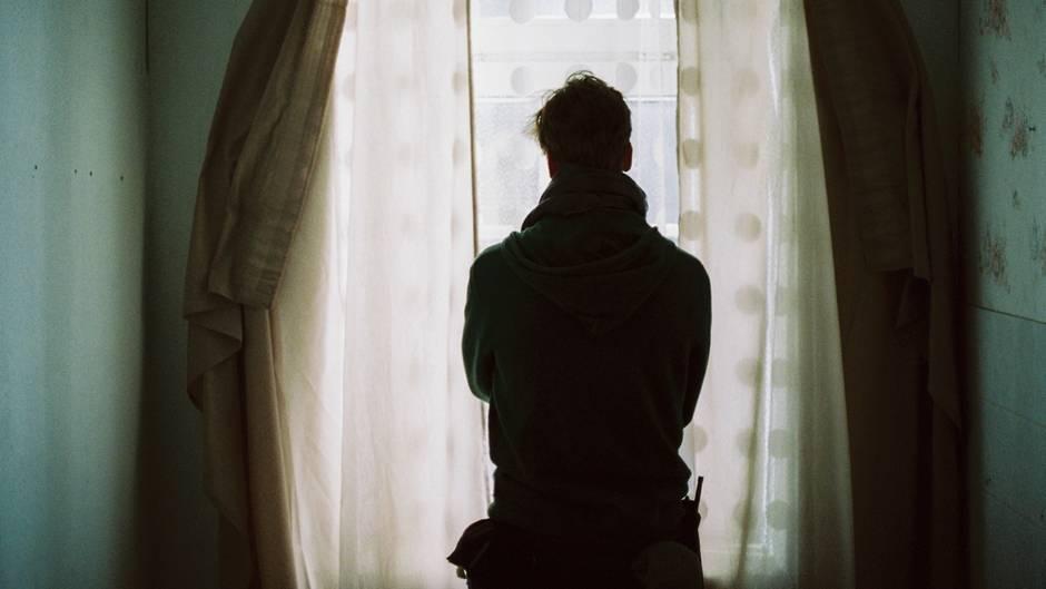 Ein Mann steht am Fenster und ist von hinten zu sehen