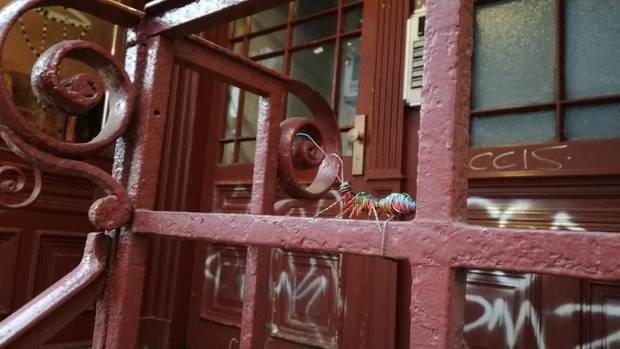 Eine Drahtameise sitzt auf einem Türgatter