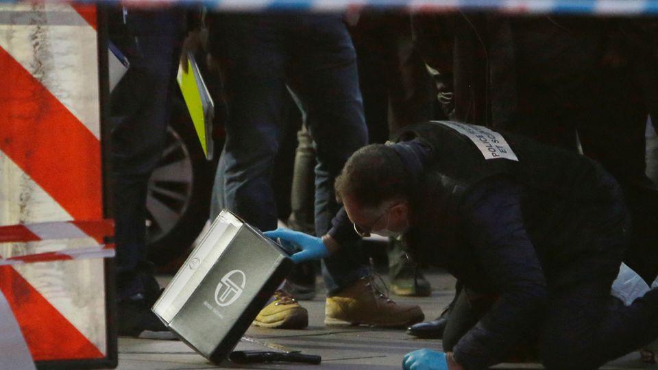 Ein Polizist untersucht eine Waffe, die auf dem Bürgersteig liegt.