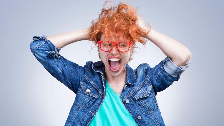 Junge Frau zerwuschelt schreiend ihre Haare