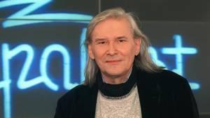 """Vor einem Neon-Schriftzug"""" Rockpalast"""" schaut Peter Rüchel mit grauen, schulterlangen Haaren in die Kamera"""