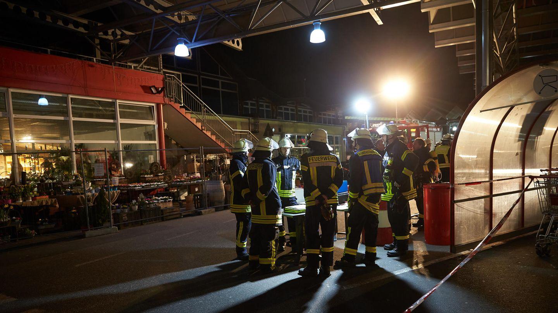 Mehrere Feuerwehrleute stehen im Scheinwerferlicht auf dem Parkplatz eines Einkaufszentrum in Unkel