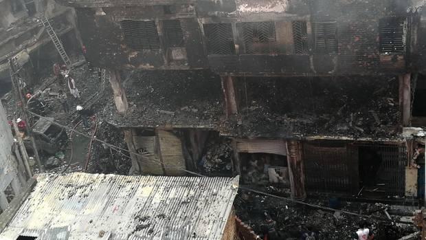 Menschen stehen nach einem Brand in der Nähe eines von den Flammen zerstörten Gebäudes in Bangladeschs Hauptstadt Dhaka
