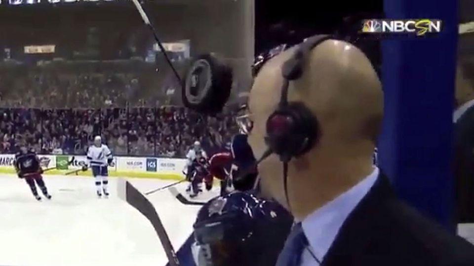 Ein Eishockey-Puck fliegt nur Zentimeter an der Stirn eines TV-Kommentators vorbei