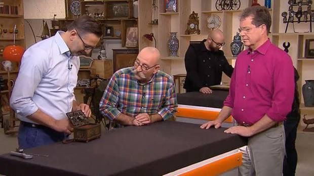 Verkäufer Markus Andree und Horst Lichter sehen sich Schatztruhe an
