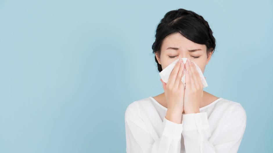 Heuschnupfen: Eine Frau benutzt ein Taschentuch