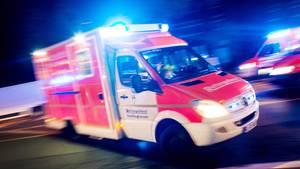 Ein Rettungswagen rast mit Blaulicht durch die Dunkelheit