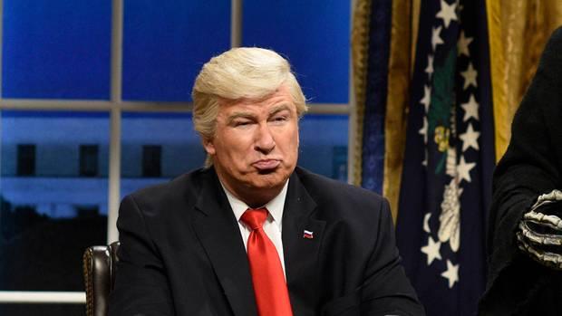 Schauspieler Alec Baldwin sitzt als Donald Trump in einer Kulisse, die ans Oval Office erinnert