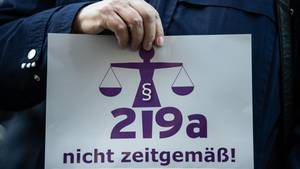 """Eine Frauenhand hält ein Pappschild mit der Aufschrift """"§219a nicht zeitgemäß"""""""