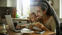 Ein Kind sitzt auf dem Schoss seiner Mutter in der Küche