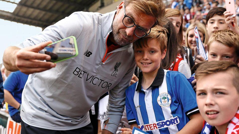 Seltene Nähe: Klopp geht ungern auf seine Fans zu. Bei diesem jungen Anhänger des Zweitliga-Klubs Wigan Athletic machte er eine Ausnahme.