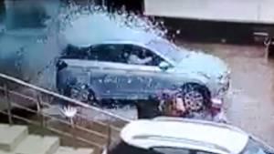 Frau fährt Auto durch ein Schaufenster