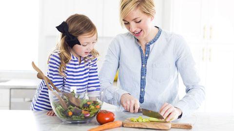 Mutter und Tochterbereiten einen Salat in der Küche vor.