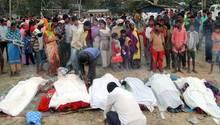 Indien, Golaghat: Menschen stehen vor den Leichen von Opfern, die an giftigem Alkohol gestorben waren