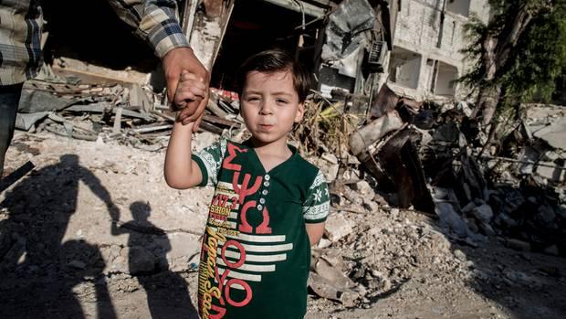 Omran hält die Hand seines Vaters, als er durch das Viertel Kaum al-Qaterdschi geht. Hier wurde er nach dem Bombeneinschlag gerettet.