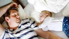 Schlaf nach der Geburt: Vater und Kind schlafen auf einem Bett