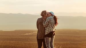 Zwei Frauen küssen sich auf einer Wiese