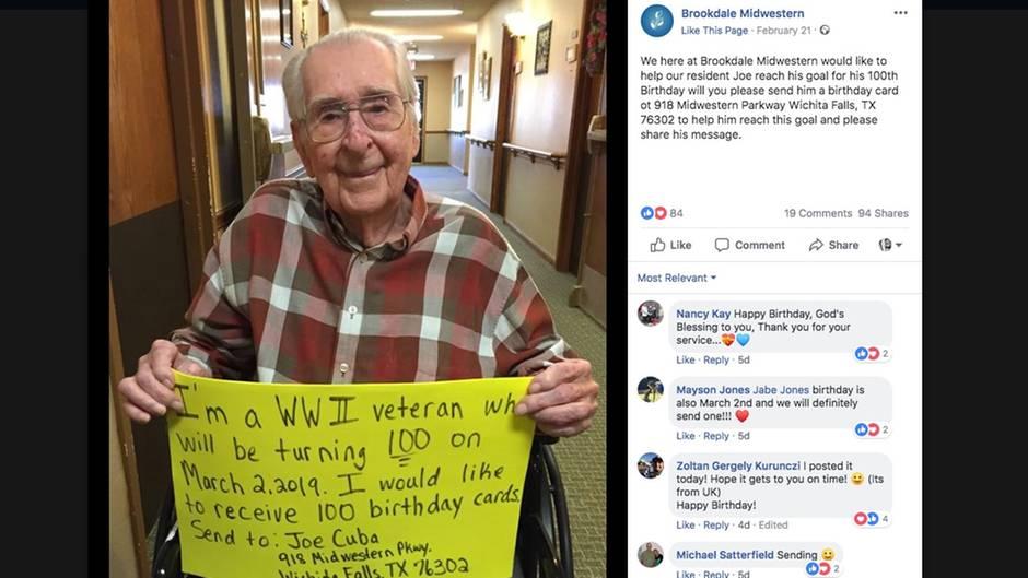 Joe Cuba sitzt im Rollstuhl und hält ein neongelbes Schild hoch