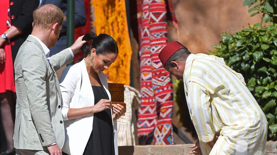 Mit der linken Hand befreit Prinz Harry - im hellgrauen Anzug - die Haare seiner Frau Meghan aus einer silbernen Halskette