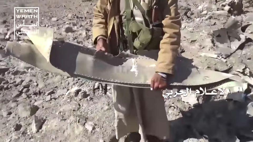 Ein jemenitischer Rebell hält die Reste desFlügels eines abgestürzten Tornado-Jets ins Bild