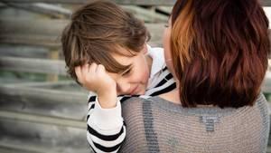 Eine Mutter trägt ihren Sohn auf dem Arm