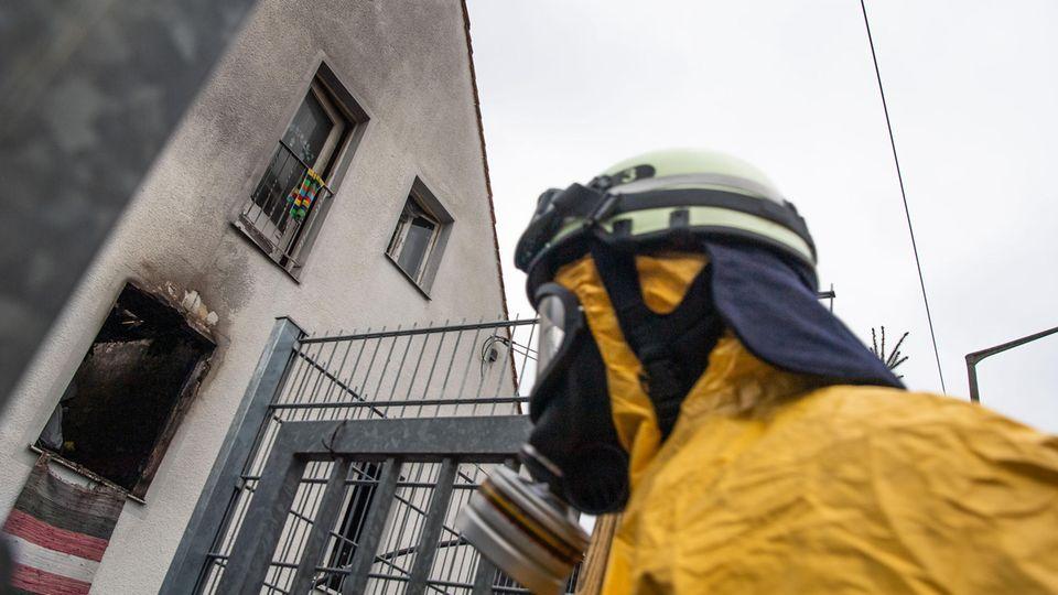 Ein Feuerwehrmann in Atemschutzkleidung geht zu dem ausgebrannten Haus