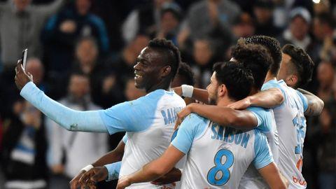 Fußballer in hellblau-weißen Trikots von Olympique Marseille stehen in einer Gruppe zusammen. Einer hält ein Smartphone hoch