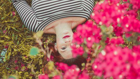 Ein Mädchen liegt in einer Blumenwiese