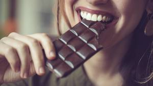 Frau, die mit einem Lächeln in Schokolade beißt