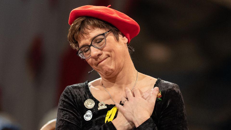 Die Bundesvorsitzende der CDU, Annegret Kramp-Karrenbauer, steht vor dem Narrengericht und verzieht das Gesicht.