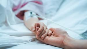 Eine Person hält einer kranken Person im Krankenbett die Hand