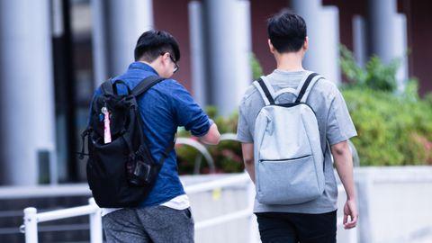 Zwei Jugendliche von hinten mit Rucksäcken