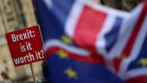 """Eine EU- und eine Großbritannienflagge. Im Hintergrund ein Protestschild mit der Aufschrift """"Brexit: is it worth it?"""""""