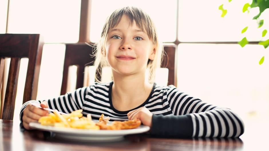 Ein Mädchen isst Pommes frites und strahlt in die Kamera