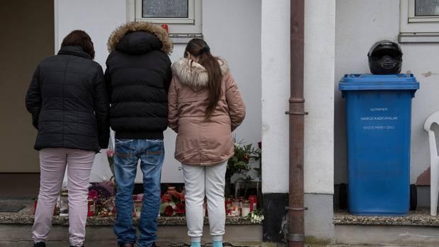 Trauernde Nachbarn und Freunde stehen vor dem Haus in Worms, in dem eine 21-Jährige getötet worden war