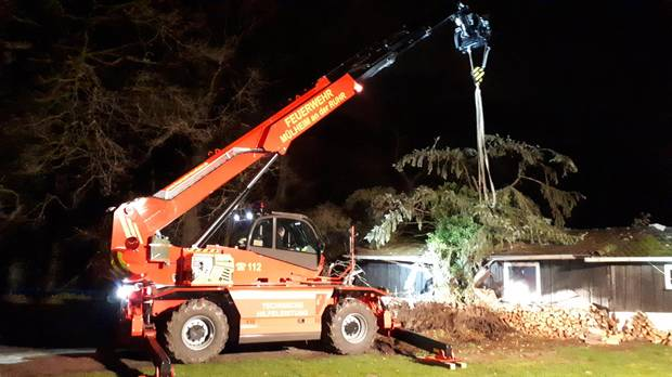 Die Feuerwehr musste den Baum mit Hilfe eines Teleskopladers vom Dach hieven
