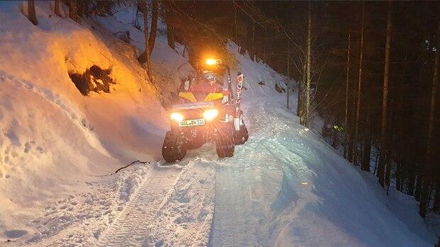Ein All-Terrain-Vehicle bei Dunkelheit im Schnee